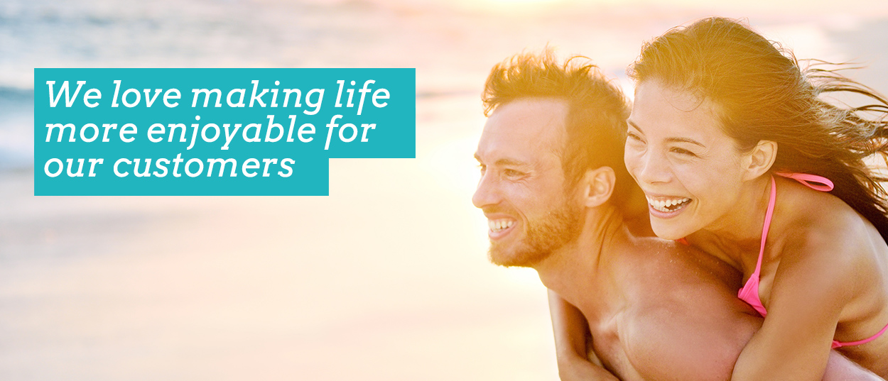 We (SlumberTrek) love making life more enjoyable for our customers. Image shows couple smiling on the beach.