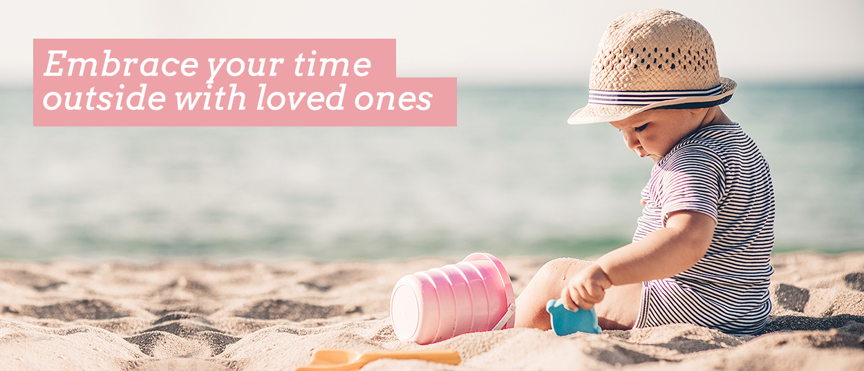 Embrace your time outside with loved ones. Image shows baby in hat playing with bucket and spade in the sand at the beach