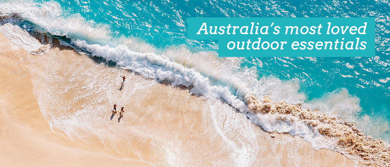 SlumberTrek - Australia's most loved outdoor essentials. Image of wave crashing along beach from above with 3 people running.