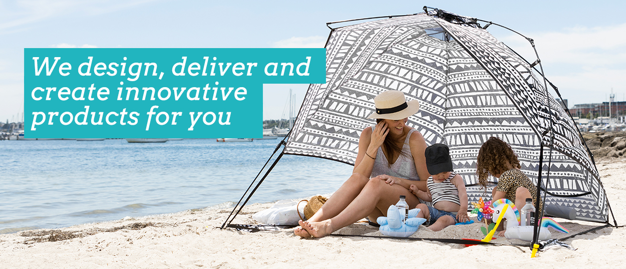 We (SlumberTrek) design, deliver and create innovative products for you. Image displays family at the beach in the shade of a geometric print Bermuda Vienna Woods Auto Ezee Sun Shelter