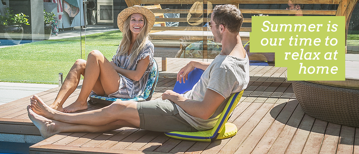 Summer is our time to relax at home. Image shows h appy couple by the pool at home seated on cushion recliners