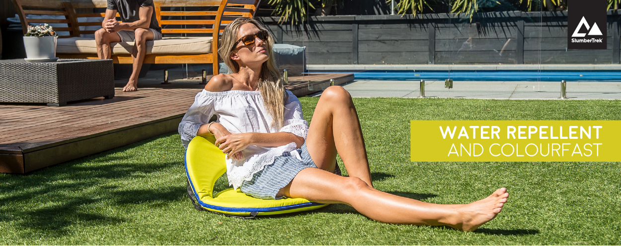 A woman soaks up the sun seated on a comfortable, padded yellow cushion recliner chair with blue trim - water repellent and colourfast.