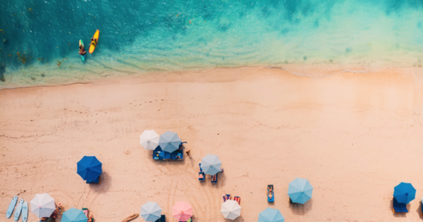 Sandy beach and shoreline from above with multiple blue shade umbrellas and two paddleboarders